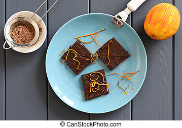Yummy handmade chocolate candy bars with orange peels on turquoise plate