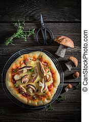 Yummy rustic pizza with noble mushrooms and thyme