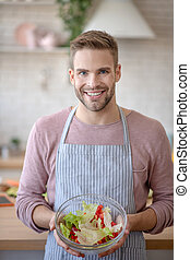 Cheerful man showing bowl with yummy vegetable salad