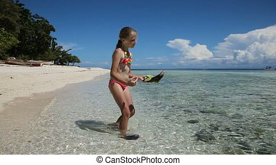 Yuong girl playing with toy ship on the beach