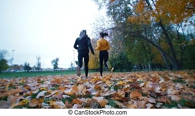 Young fit women running away from the camera in the autumn park.