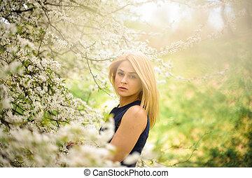zärtlich, blond, frauenansehen, auf, der, unscharfer hintergrund, von, a, weißes, blühen, kirschbaum