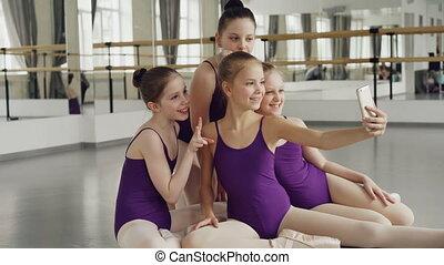złamanie, mały, smartphone, podłoga, selfie, posiedzenie, dziewczyny, balet, bodysuits, patrząc, znowu, przedstawianie, ładny, między, webcam, studio, classes., podczas, wpływy