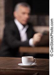 złamanie, time., dojrzały, biznesmen, czytanie gazeta, z, niejaki, filiżanka kawowa, na, przedimek określony przed rzeczownikami, pierwszy plan