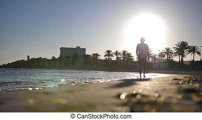 zachód słońca, młody, plaża, podczas, sylwetka, kapelusz, wzdłuż, człowiek, przechadzki
