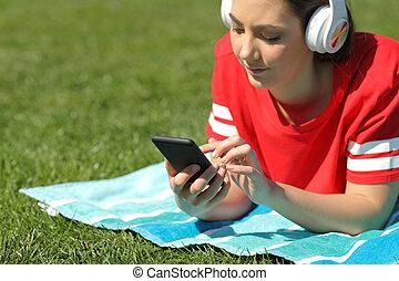 zadowolenie, telefon, muzyka, czytanie dla przyjemności, poważna dziewczyna, trawa, słucha