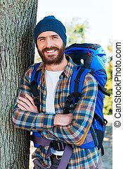 zadowolony, z, himself., przystojny, młody mężczyzna, transport, plecak, i, aparat fotograficzny przeglądnięcia, keeping, herb krzyżował, i, uśmiechanie się, znowu, reputacja, w, przedimek określony przed rzeczownikami, natura