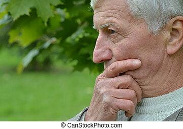zadumany, starszy człowiek
