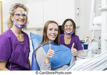 zahnärzte, lächeln, während, patient, gesturing, daumen hoch, in, klinik