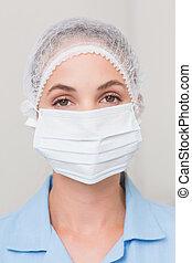 zahnarzt, in, chirurgische maske, und, kappe, anschauen kamera