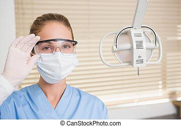 zahnarzt, in, chirurgische maske, und, schützende gläser, anschauen camer