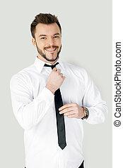 zakelijk, aankleding, boven., mooi, jonge man, in, formalwear, aanpassen, zijn, stropdas, en, kijken naar van fototoestel, terwijl, staand, tegen, grijze , achtergrond