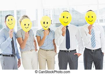 zakenlui, vasthouden, vrolijke , glimlachen, voor, gezichten