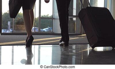 zakenlui, verwaarlozing, luchthaven, door, automatisch, glas deur, met, hun, luggage., jonge man, en, vrouw, in, heels, wandelende, van, terminal, en, rol, koffer, op, wheels., concept, van, werken, trip., slowmotion