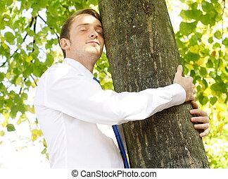zakenman, boom omhelzend