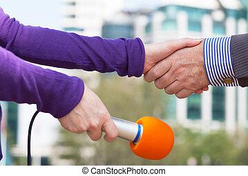 zakenman, en, een, vrouwlijk, reporter, schuddende handen, voor, media, interview