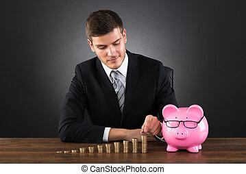zakenman, met, piggybank, stapelen, muntjes