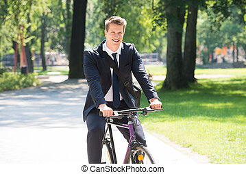 zakenman, rijdende fiets, in park