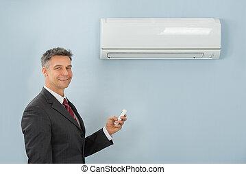 zakenman, vasthouden, afstandsbediening, klimaatregelaar, in, kantoor