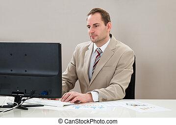 zakenman, werkend aan computer