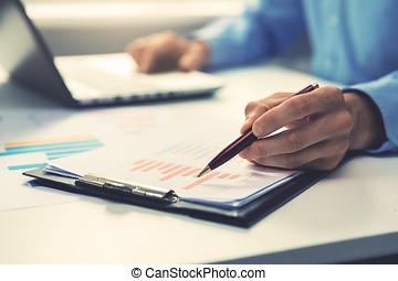 zakenman, wijzende, met, pen, op, jaarlijks, handel melding, tabel