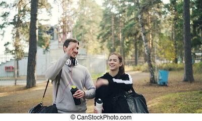 zakken, wandelende, buiten, dan, na, park, jonge, mooi, high-five., klesten, zijn, lachen, vrouwlijk, opleiding, sporten, headphones, vriend, man