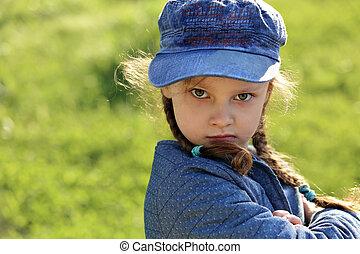 zangado, sério, criança, menina, em, chapéu azul, grimacing, ligado, verão, grama verde, experiência., closeup, retrato