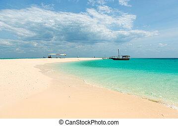Zanzibar beach and touristic boats in the ocean - colorful...