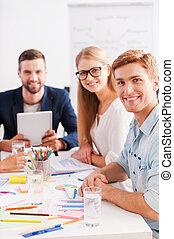 zaufany, i, creative., grupa, od, radosny, handlowy zaludniają, w, przemądrzały przypadkowy, nosić, posiedzenie razem, na stole, i, aparat fotograficzny przeglądnięcia