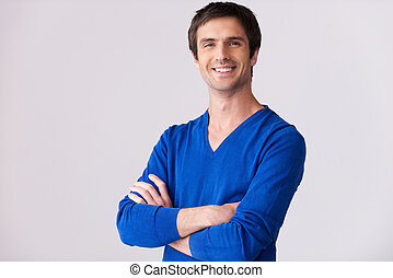 zaufany, i, handsome., radosny, młody mężczyzna, w, błękitny, sweter, aparat fotograficzny przeglądnięcia, i, keeping, herb krzyżował, znowu, reputacja, przeciw, szary, tło