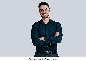 zaufany, manager., przystojny, młody mężczyzna, w, koszula, keeping, herb krzyżował, i, aparat fotograficzny przeglądnięcia, znowu, reputacja, przeciw, szary, tło