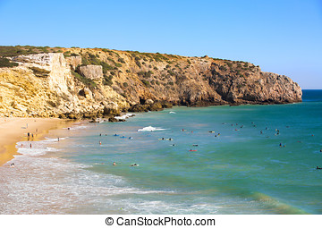 Zavial beach in Portugal with lot of surfers in ocean