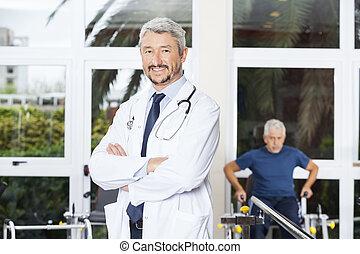 zeker, fysiotherapeut, staand, gekruiste wapens, in, rehab, centrum