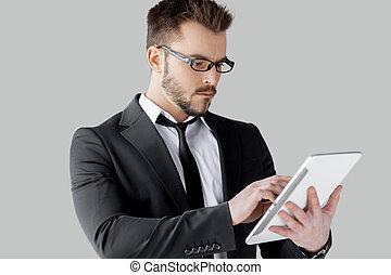 zeker, in, zijn, gadget., vrolijk, jonge man, in, formalwear, en, bril, doorwerken, digitaal tablet, terwijl, staand, tegen, grijze , achtergrond
