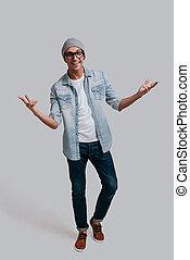 zeker, in, zijn, style., volledige lengte, van, mooi, jonge man, in, jeans, hemd, gesturing, en, kijken naar van fototoestel, terwijl, staand, tegen, grijze , achtergrond