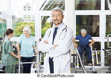 zeker, mannelijke , fysiotherapeut, staand, gekruiste wapens, in, rehab, ce