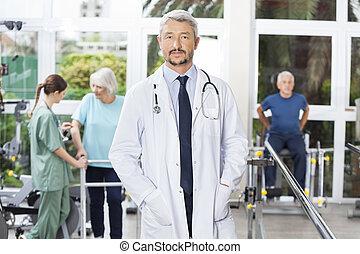 zeker, mannelijke , fysiotherapeut, staand, in, rehab, centrum