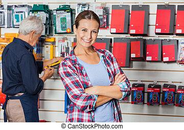 zeker, vrouw, met, gekruiste wapens, in, hardware winkel