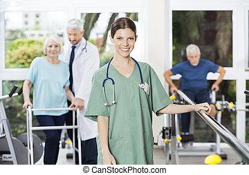 zeker, vrouwlijk, fysiotherapeut, staand, in, rehab, centrum