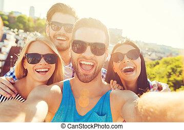 zelfs, voor, fun., groep, van, vrolijk, jongeren, bonding, om te, elkaar, en, vervaardiging, selfieon, fototoestel, terwijl, hebbend plezier, op, de, dak