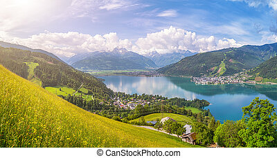 Beautiful panoramic view of the famous city of Zell am See with idyllic Zeller Lake and blooming meadows on a sunny spring day in Salzburg, Salzburger Land, Austria