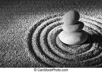 Three stacked stones on raked sand