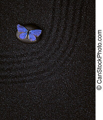 Zen garden with wave lines in the black sand with a blue butterfly
