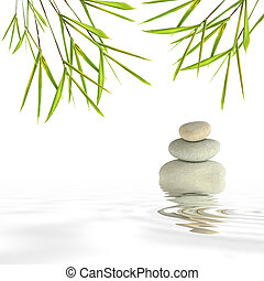 Zen abstract of gray spa stones in perfect balance and bamboo leaf grass with reflection over rippled water, against a white background.