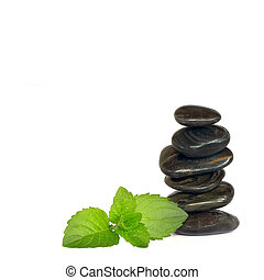 Black spa massage stones in perfect balance and lemon balm leaf herb sprig, over white background.