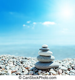 zen-like stones on beach and sun in sky. soft focus on...