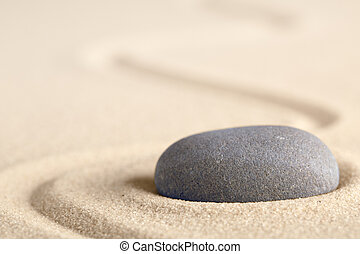 Zen meditation stone with raked line in sand