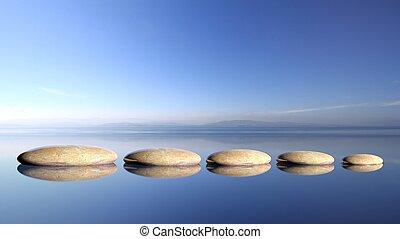 zen, piedras, fila, de, grande, a, pequeño, en, agua, con, cielo azul, y, pacífico, paisaje, fondo.