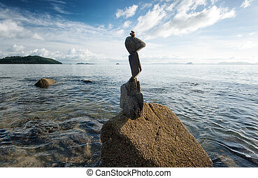 Zen rock tower on sea cost morning sunrise time. Nature landscape photography