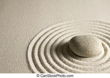 Zen stone - Close-up of a stone on raked sand; zen concept